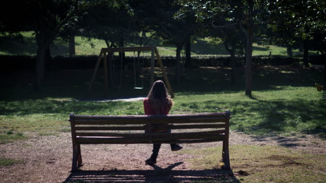 lonely sad woman sitting on bench in the park,thinking her abortion video
