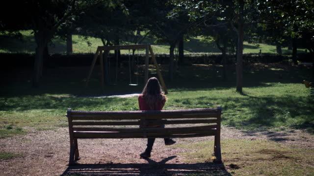 einsame traurige Frau sitzt auf der Bank im Park, denken ihre Abtreibung – Video