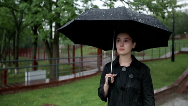 stockvideo's en b-roll-footage met lonely sad woman standing on the street under heavy rain. - funeral crying
