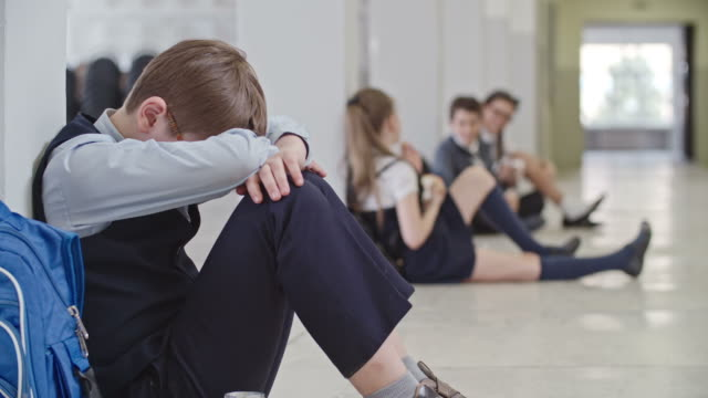 Lonely Schoolboy Sitting in Hallway Selective focus of miserable schoolboy in uniform sitting alone on floor in school hallway with head on knees crying and feeling lonely, chatting and laughing classmates in background depression land feature stock videos & royalty-free footage