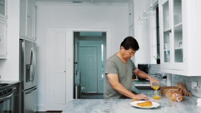 Lonely senior male widower prepares breakfast