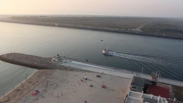 vídeos de stock e filmes b-roll de lonely ship gently cruising a lagoon next to a beach. barra beach from aveiro, portugal. - aveiro
