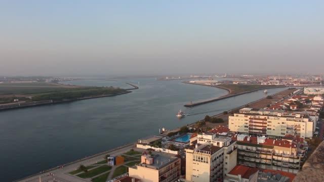 vídeos de stock e filmes b-roll de lonely ship gently cruising the aveiro lagoon, with lovely mediterranean town next to it. aveiro, portugal. - aveiro