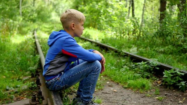 a lonely teenage boy sitting on railroad tracks - solo bambini maschi video stock e b–roll