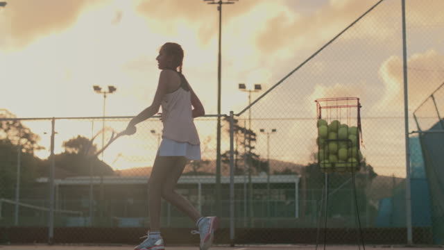 lonely tennis player practising hard into the night - praticare video stock e b–roll