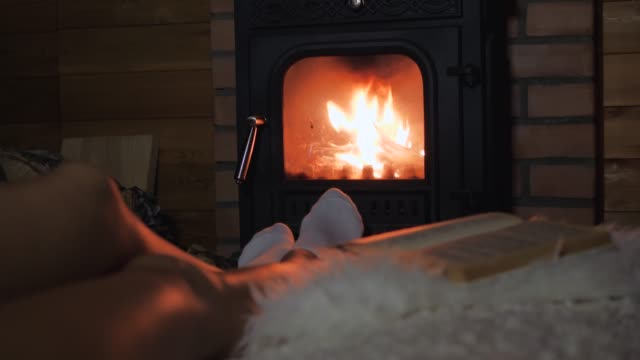 lonely woman is lying in front of the fireplace and drinking wine from a glass - calzino video stock e b–roll