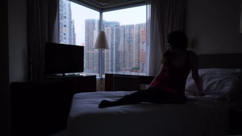 vídeos y material grabado en eventos de stock de mujer sola sentada en la cama y mirando en la ventana - feminidad