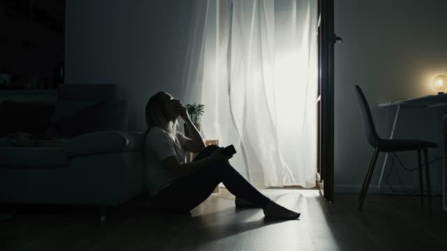 自ら隔離する時間の間に床に座っているds孤独な女性 - 寂しさ点の映像素材/bロール