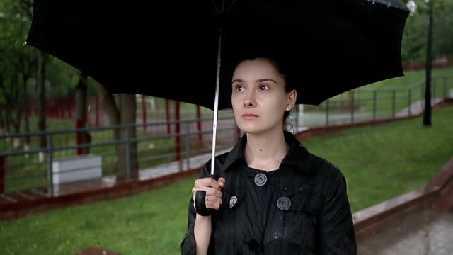 stockvideo's en b-roll-footage met lonely woman standing on street in heavy rain. slow motion - funeral crying