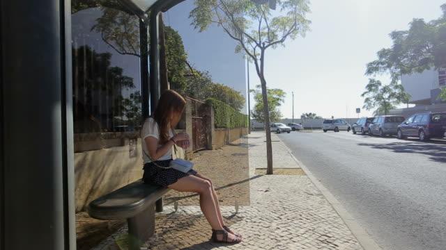 vídeos y material grabado en eventos de stock de lonely young girl espera que se hospedan en la parada de autobús en falda azul y gafas de sol, en verano, el - stop sign
