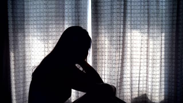暗い寝室で手に座って落ち込み、ストレスを感じている孤独な若い女性、否定的な感情とメンタルヘルスの概念 - 寂しさ点の映像素材/bロール