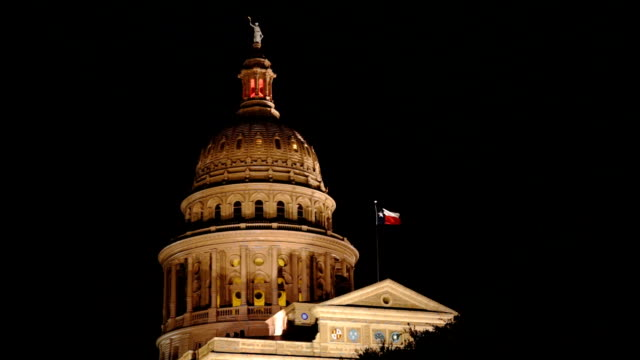lonestar state flag waves austin capital building at night - capitello video stock e b–roll