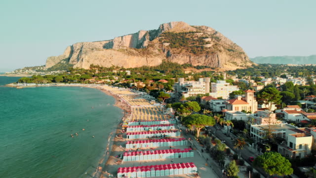 long beach by the ocean with turquoise water. on the background of the mountain and a lot of trees. sunset time. aerial drone shot - palermo città video stock e b–roll