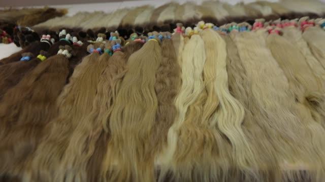 uzun güzel kadın saçı, açık tonlarında yapay uzun kadın saçı - peruk stok videoları ve detay görüntü çekimi