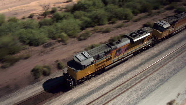 AERIAL: Long container freight train transporting goods across the country