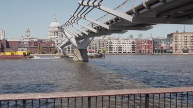 un lungo dolly girato lungo il tamigi, seguendo una barca che va sotto il millennium foot bridge - 20 o più secondi video stock e b–roll