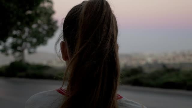 långt hår flicka vid vägkanten med bilen trafiken vänder henne tillbaka till kameran. - endast en tonårsflicka bildbanksvideor och videomaterial från bakom kulisserna