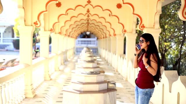Mulheres jovens de cabelocomprido falando no celular no Templo Gomatgiri, Indore, Índia - vídeo