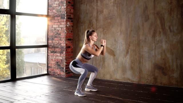Langhaarige Sportler professionell führt Kniebeugen. Kaukasische junge Frau in grauer Sportbekleidung bei körperlichen Übungen. Eine Frau zeigt, wie man Ecxact-Übungen macht. Leeres Studio mit Sonnenlicht im Hintergrund – Video