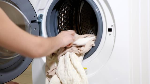 langhaarige mädchen in t-shirt nimmt saubere wäsche der modernen waschmaschine - waschmaschine wand stock-videos und b-roll-filmmaterial