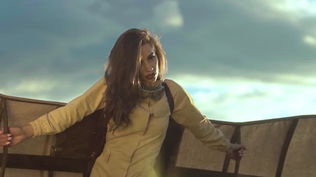 long haired woman in brown dressing shows glider wings video