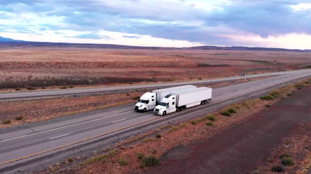 long haul freight hauler полугрузовая и прицеп путешествия по четырехполосной шоссе в пустынной пустыне в сумерках или на рассвете - колонна стоковые видео и кадры b-roll