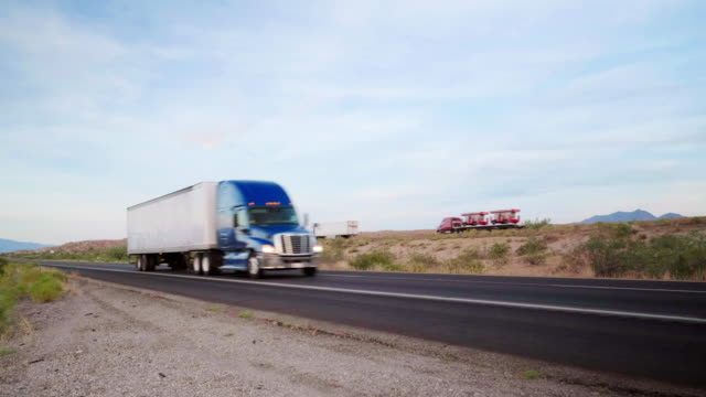 Long Haul Semi Truck On a Rural Western USA Interstate Highway Large semi truck hauling freight on the open highway in the western USA under an evening sky. semi truck stock videos & royalty-free footage