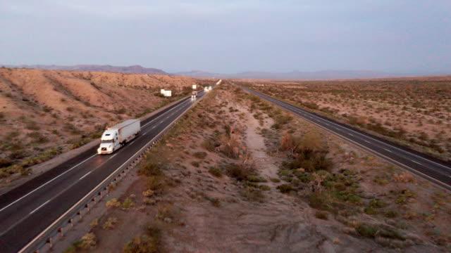long haul semi truck on a rural western usa interstate highway - колонна стоковые видео и кадры b-roll