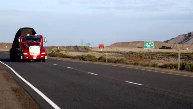 a long haul semi-truck and trailer heading down a four-lane highway in the desert at dawn or dusk - transport truck tyres video stock e b–roll