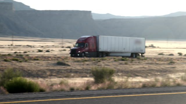 A Long Haul Semi-Truck and Trailer Heading Down a Four-Lane Highway in the Desert at Dawn or Dusk