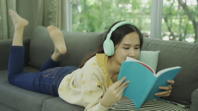 Long shot of 4K footage of young asian woman reading a book and listening to music from wireless headphones with relax on sofa in living room at home.