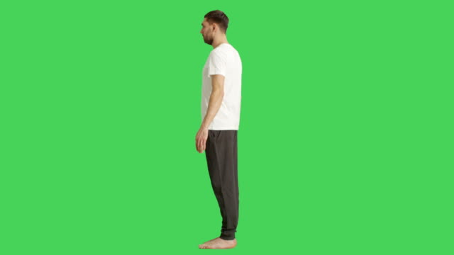 long shot of a bare foot man wearing t-shirt and sweatpants while camera rotates around him. shot on a green screen background. - maglietta video stock e b–roll