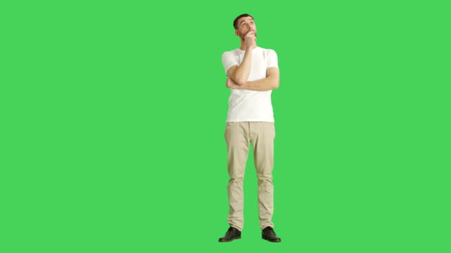 Long Shot of a Casual Man Looking Around Amused and Making Touching Chin Thinking Gesture. Shot on a Green Screen Background. video