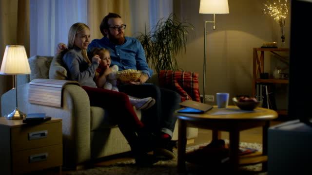 Totale von Vater, Mutter und Mädchen vor dem Fernseher. Sie sitzen auf einem Sofa in ihrem gemütlichen Wohnzimmer und Popcorn essen. Es ist Abend. – Video