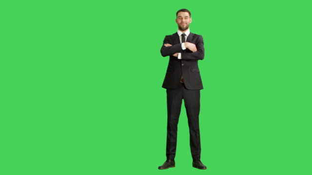 long shot of a handsome businessman crossing his arms on a chest and smiling. background is green screen. - stare in piedi video stock e b–roll