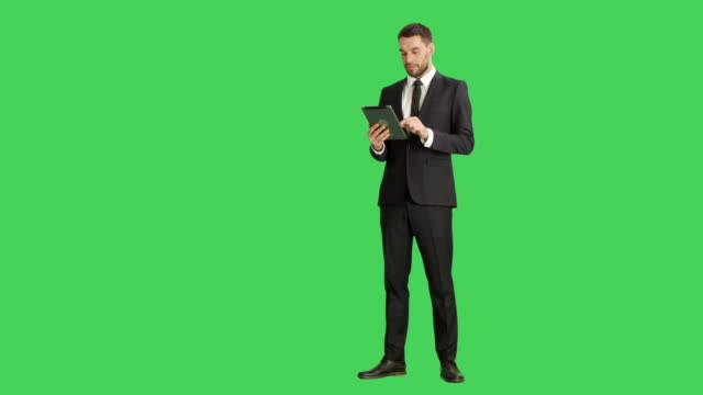 Long Shot of a Handsome Businessman Holding Tablet Computer with One Hand and Making Swiping Touching Gestures with Another. Tablet and Background are Green Screen.