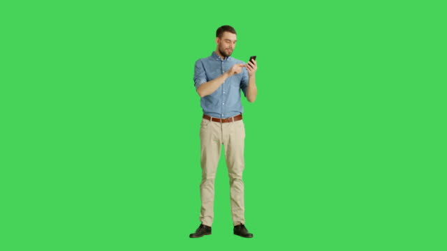 vídeos de stock e filmes b-roll de long shot of a handsome man holding smartphone with one hand and making swiping touching gestures with another. tablet and background are green screen. - teeshirt template