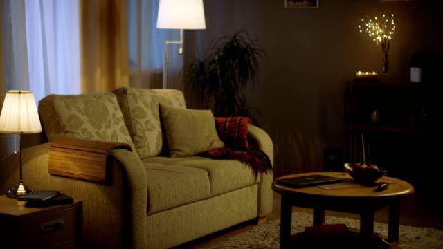 夜のリビングルームのロングショット。ライトが点灯し、色が柔らかくて居心地が良いです。 - 居間点の映像素材/bロール