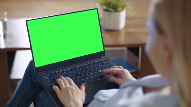 long shot of a smiling beautiful woman sitting on a couch in her living room. she works on her laptop which she holds on her lap. - cercare video stock e b–roll