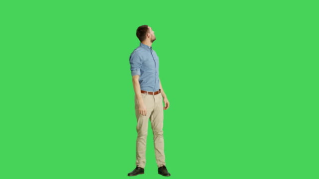Long Shot of an Amused Handsome Man Looking Around. All Shot on a Green Screen Background.