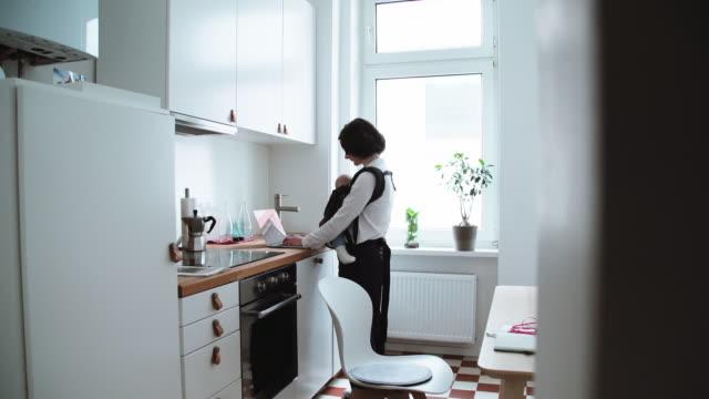 långskott av mamma stående i köket med bärbar dator och med spädbarn i bärsele - working from home bildbanksvideor och videomaterial från bakom kulisserna