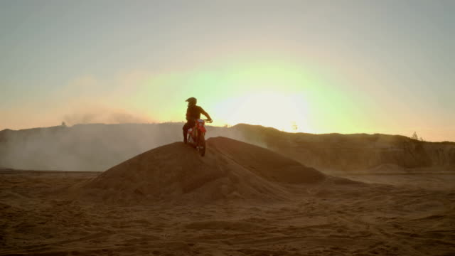 long shot of the extreme motocross rider in a cool protective helmet standing on the sand dune in the middle of scenic quarry with mist and dust covering him. - freestyle motocross video stock e b–roll
