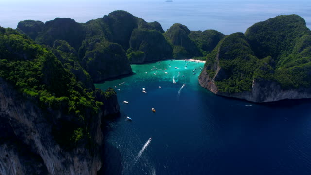 maya bay, koh phi phi leh, thailand - may 16, 2018. long tail boats mooring in the famous maya bay with tourists on the beach - phuket video stock e b–roll