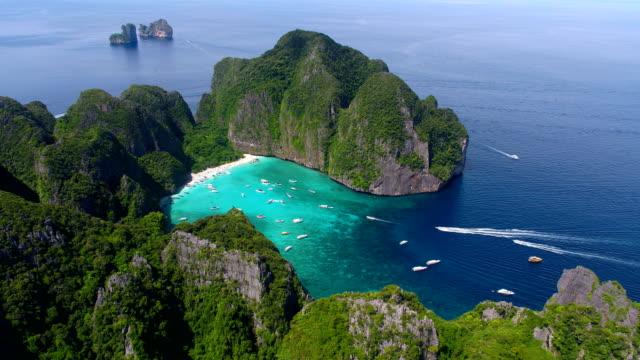 vídeos de stock e filmes b-roll de maya bay, koh phi phi leh, thailand - may 16, 2018. long tail boats mooring in the famous maya bay with tourists on the beach - phuket