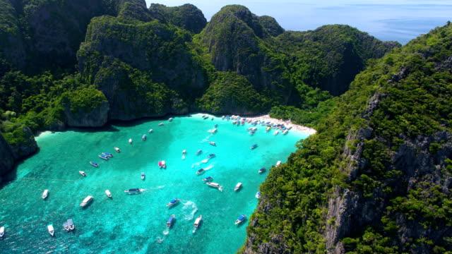 vídeos de stock, filmes e b-roll de maya bay, koh phi phi leh, tailândia - 16 de maio de 2018. barcos de cauda longa, amarração na famosa baía maya com turistas na praia - phuket