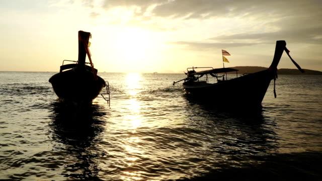lange schwanzboote mit ruhiger meeresoberfläche bei sonnenuntergang - indochina stock-videos und b-roll-filmmaterial