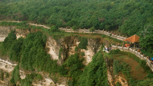 Long tourist road is located along the cliffs above the ocean. A large number of people walking on a footpath in a green nature reserve video