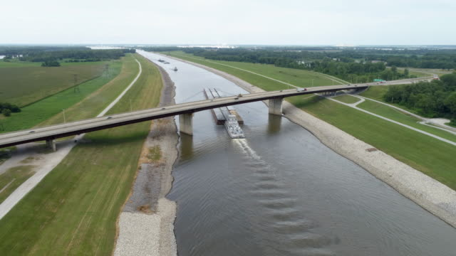 Long tow is running under a highway bridge on the Chain of Rocks Cana A long tow is running under a highway bridge on the Chain of Rocks Canal above St Louis, aerial view towing stock videos & royalty-free footage