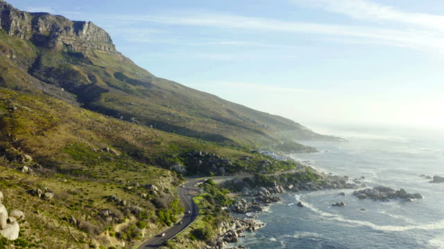 Long winding roads to new places are my favourite 4k video footage of a busy road at the foot of Cape Town's mountain range which is surrounded by sea cape town stock videos & royalty-free footage