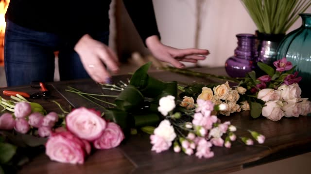 Longhaired brunette florist preparing flowers for her future bouquet. Arranging different flowers on table - tulips, roses, tea roses. Fireplace on the background